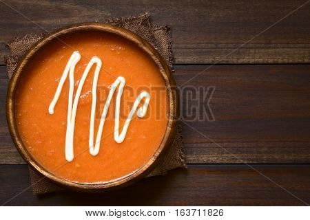 Homemade fresh cream of tomato soup served in wooden bowl photographed overhead on dark wood with natural light (Selective Focus Focus on the top of the soup)