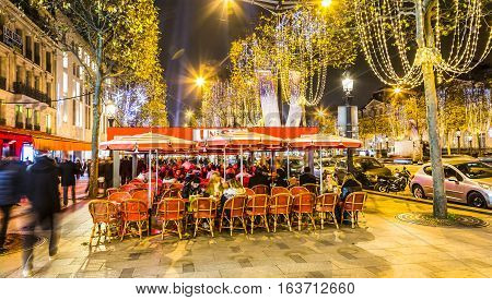 ParisFrance - 27 November 2016: Unidentified people spending time on a street terrace on the famous Parisian Champs Elysees Boulevard during a night in the winter holidays season.