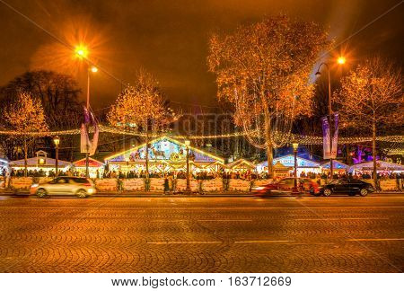 ParisFrance - 27 November 2016: Blured traffic and traditional kiosks on the famous Champs Elysees Boulevard in Paris festive decorated during the winter holidays.