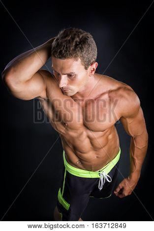 Handsome shirtless bodybuilder smiling at camera on dark, smoky background
