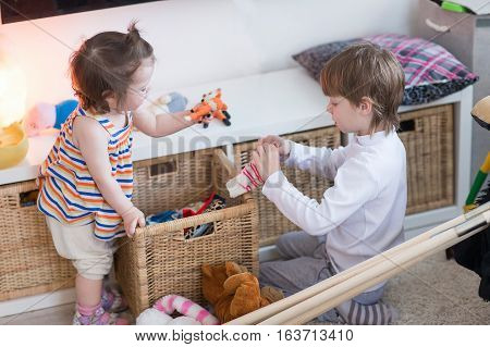 Brother and sister playing in the nursery in the afternoon in a country house.