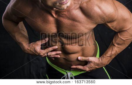 Handsome shirtless bodybuilder's abs on dark background