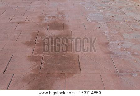 Stamped concrete floor outdoor pavement worn out, appearance of natural stone, mimics colors and textures of material pavers, red square pattern wet and humid