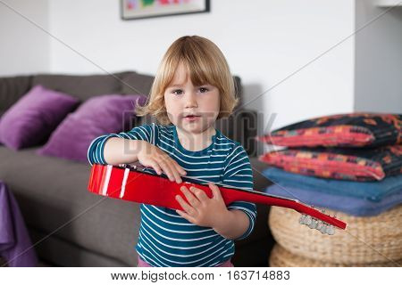Little Child With Red Guitar Looking