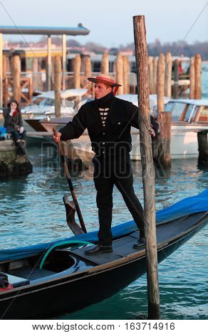 Venice,Italy - February, 25th 2011:A young gondolier pushes a wooden pole to move his gondola on a canal in Venice near San Marco Square.