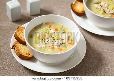 Chicken and potato chowder soup with green bell pepper and carrot in bowls with toasted bread slices on the side photographed with natural light (Selective Focus Focus one third into the first soup)