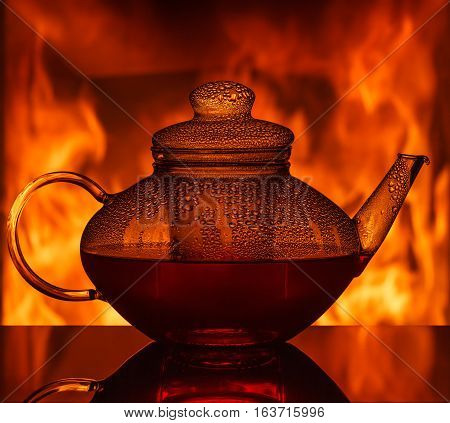 A glass teapot at the table in front of a fireplace