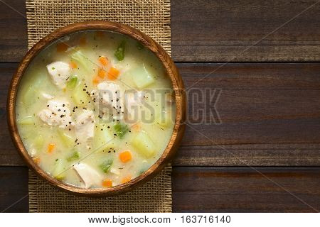 Chicken and potato chowder soup with green bell pepper and carrot in wooden bowl photographed overhead on dark wood with natural light (Selective Focus Focus on the soup)