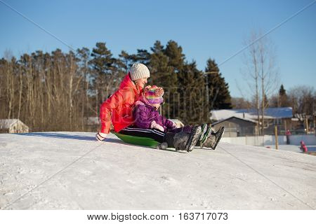 Close up side profile of four year old girl and her teenage sister having fun sliding down a hill in winter