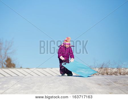 Four year old happy girl sliding downhill on a crazy carpet on a winter hill