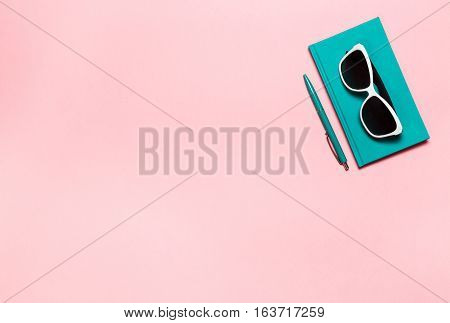 flat lay photo of workspace desk with aquamarine notebook, eyeglasses, with copy space pink background, minimal style.