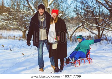 Happy family having fun snowy woodland outdoor.