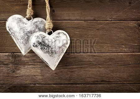 Two Rustic Metal Heart Ornaments Hanging Against A Vintage Wooden Background