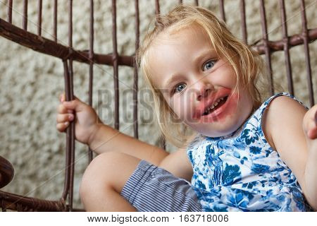 A 3 year old girl has smeared a lipstick over face