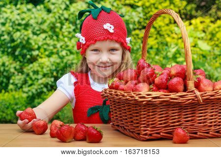 A funny little girl 4 years old in a red sundress, with a strawberry hat and a basket of strawberries