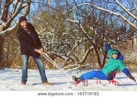 Active man and boy playing in winter park. Father rolls his son on a sledge.