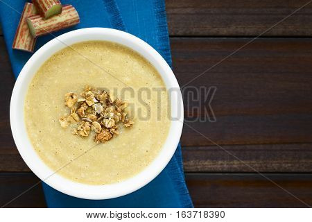 Fresh homemade sweet rhubarb mousse desserts with crunchy granola on top served in bowl photographed overhead on dark wood with natural light (Selective Focus Focus on the top of the dessert)