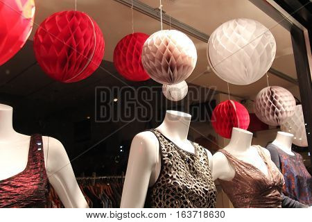festive holiday display in window with pretty dressed mannequins