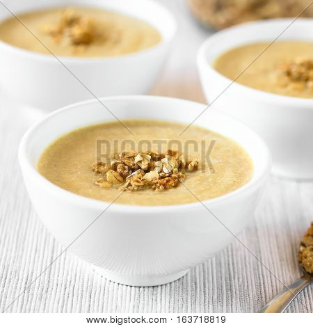 Fresh homemade sweet rhubarb mousse dessert with crunchy granola on top served in bowls photographed with natural light (Selective Focus Focus in the middle of the first dessert)