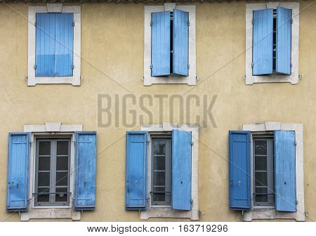 Old yellow stucco house with blue shutters