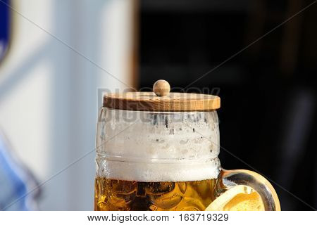 Large beer in a glass with a wooden lid