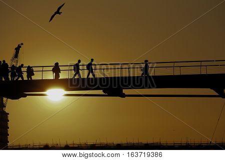 silhouette of people walking across a bridge in a golden sunset