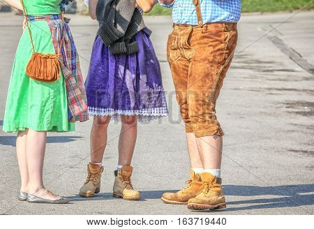 Two women in dirndl skirts and a man in lederhosen at Octoberfest