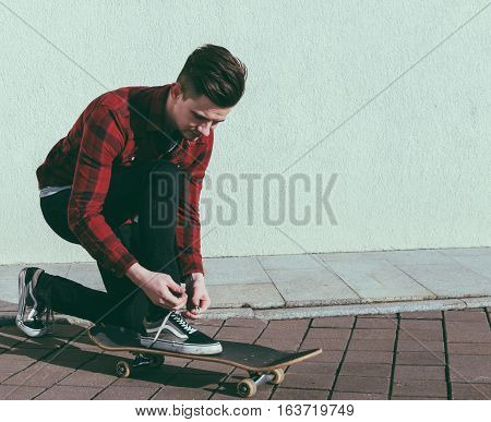 Young man tying a shoelaces on the street