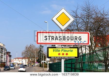 STRASBOURG FRANCE - MAR 20 2016: Strasbourg Ville Fleurie sign - translating as Blooming City - at the entrance of Strasbourg Alsace France with cars and houses in the background