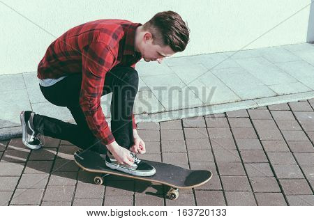 Young man skater tying a shoelaces on the street
