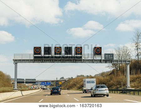 GERMANY - MAR 26 2016: Driver point of view pov of cars trucks and motorcycles driving on German Autobahn Bundesautobahn or Federal Motorway highway with speed limits of 120 kmh electronic street sign