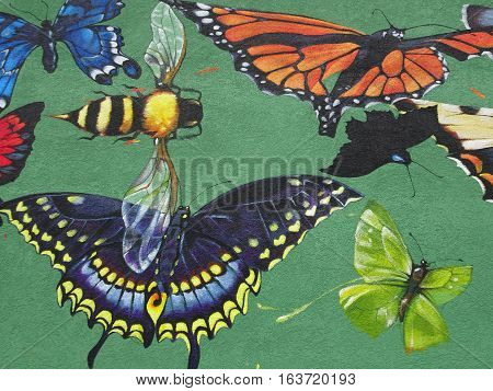Public art, detailing the vibrant colors, patterns, repeated and balanced shapes of butterflies surrounding a colorful yellow and black striped bee, inspires viewers in this midwest town with the beauty of nature.