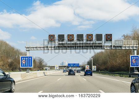 GERMANY - MAR 26 2016: Driver point of view pov of cars trucks and motorcycles driving on German Autobahn Bundesautobahn or Federal Motorway highway with speed limits of 100 kmh electronic street sign
