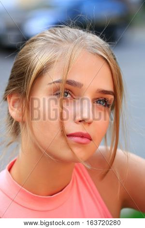 Pretty young woman or girl with tied in bun blonde hair in pink shirt with cute face on sunny day