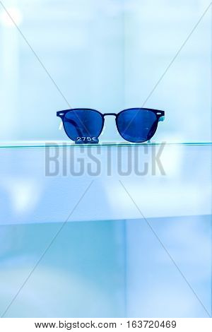 Trendy fashion sunglasses in window store with price tag on blue background