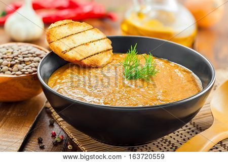 Lentil cream soup on wooden table healthy food cooking