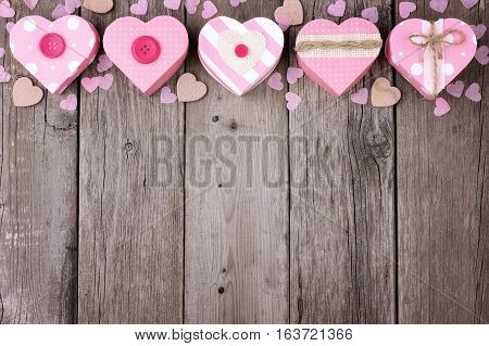 Valentines Day Top Border Of Heart Shaped Gift Boxes With Soft Pink And Burlap Trim Over Wood