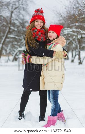 two happy girls playing on the snow in winter day outdoor.