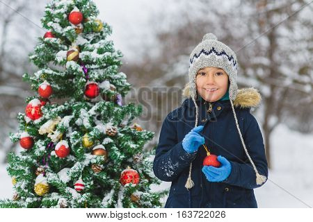 Cute little child or preschool boy decorating christmas tree outdoor.
