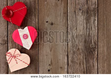 Valentines Day Side Border Of Heart Shaped Gift Boxes With Red And Burlap Trim Over Wood