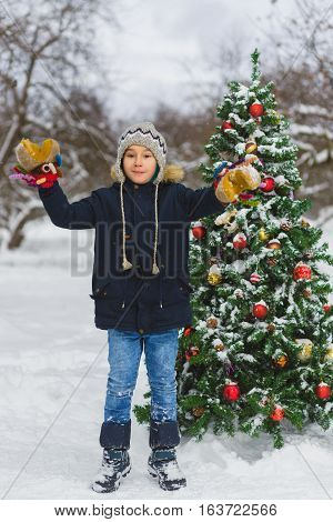 Cute little preschool boy jumping or playing near christmas tree outdoor.