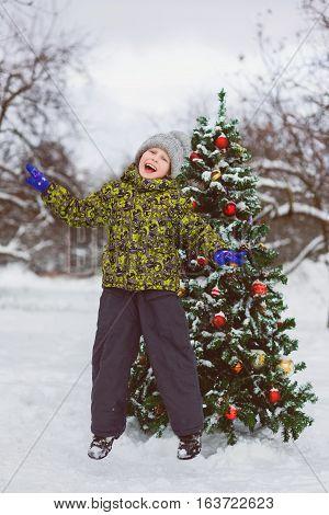 Cute little preschool boy jumping or playing near christmas tree outdoor.