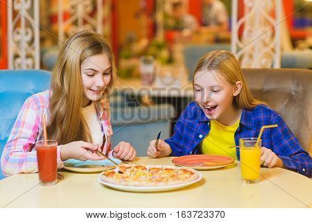 Two smiling girls eating pizza and drinking juice indoor.