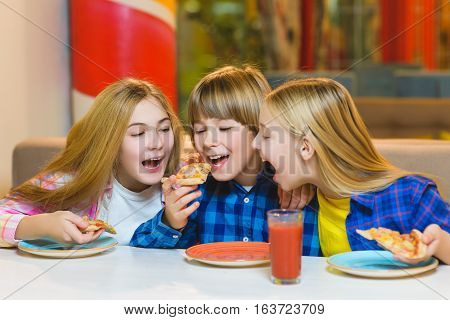 smiling boy and girls eating pizza or drinking juice indoor.
