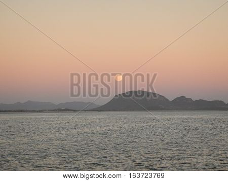 View of moon rising over a mountain from the ocean.