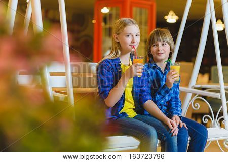 two teenagers or happy kids - boy and girl drinking juice in cafe.