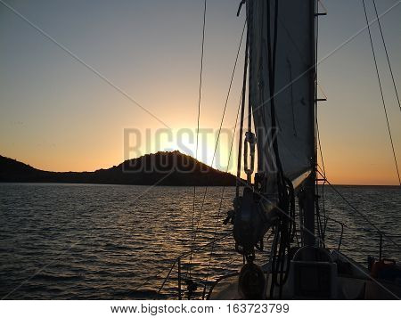 Sunset behind islands looking through sailboat rigging and sails.