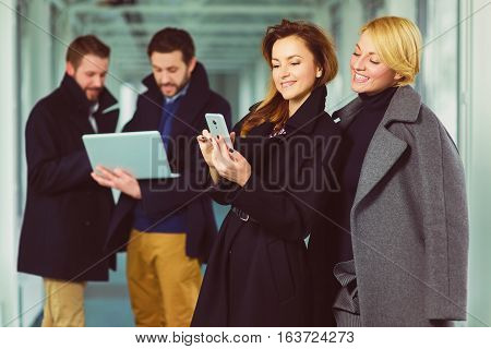 Two businesswoman looking smart phone in lobby with colleagues at background.