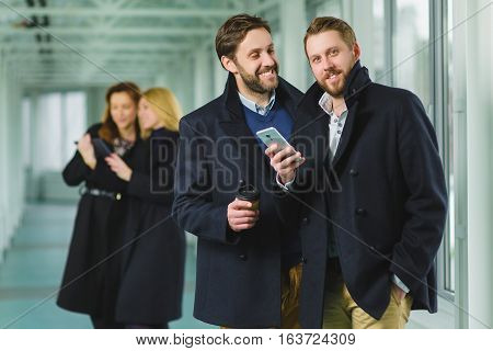 Two businessman holding smart phone in lobby with colleagues at background.
