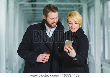 Elegant couple dressed in coat looking on smart phone at lobby.